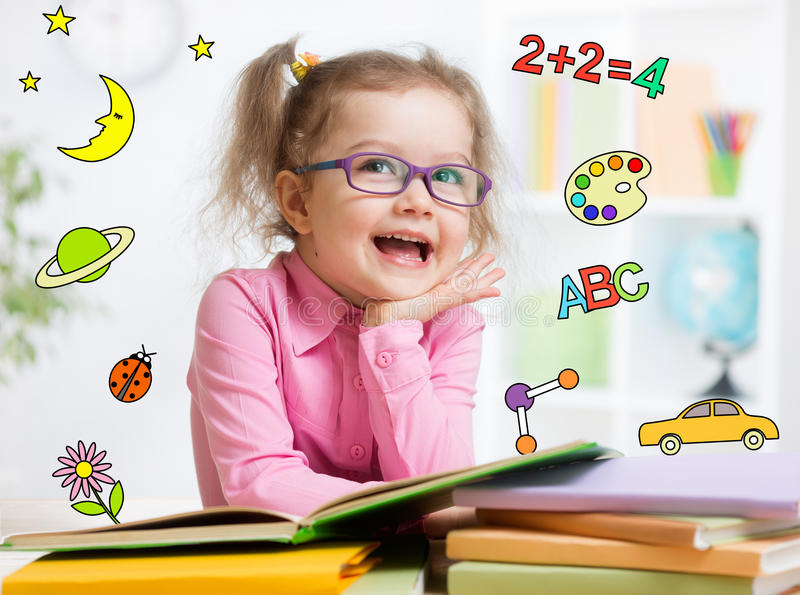 Funny smart kid in glasses reading book in stock photography
