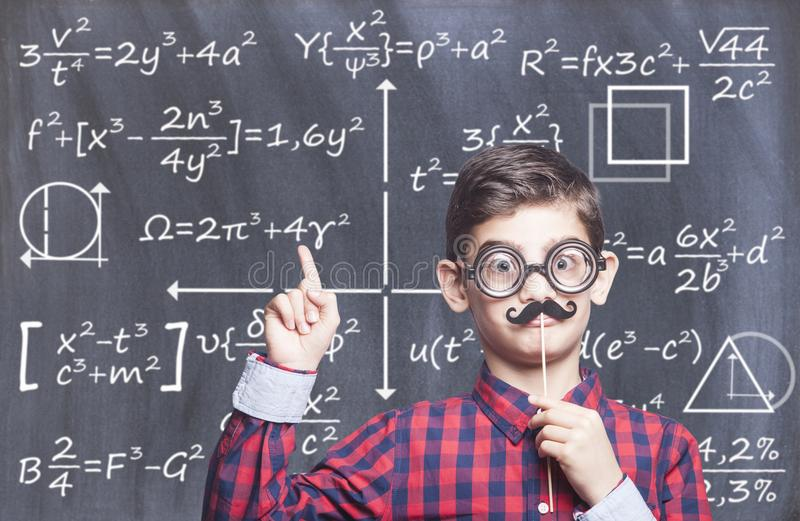 Education concept. Funny smart school boy in front of a blackboard stock images