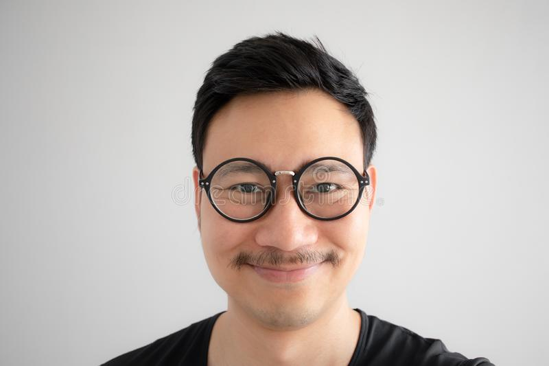Funny smile face of Asian nerd guy with eyeglasses and mustache royalty free stock photo