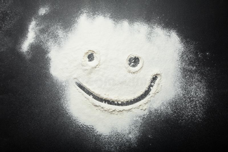 Funny smiley painted with a finger on the flour stock images