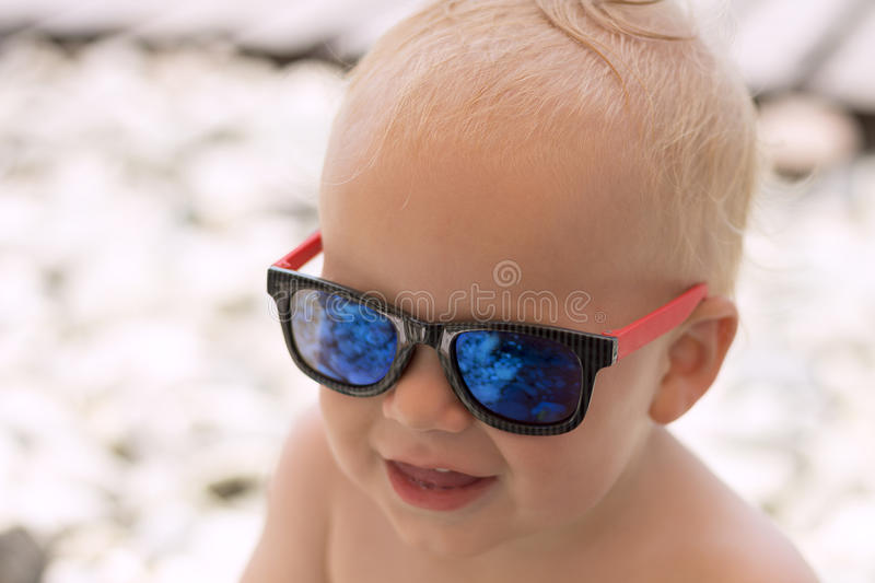Funny smiling baby boy in sunglasses on the beach. Stones are reflected in the glasses. Little boss on vacation.  stock photos