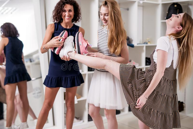 Funny smiling girlfriends having fun in boutique offering new footwear to their friend lifting her leg to check the size. By putting shoes sole-to-sole royalty free stock image