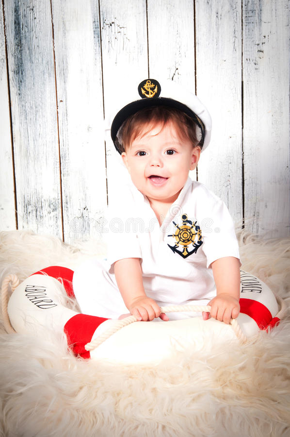 Funny smiling little boy dressed as a sea captain in naval cap. royalty free stock photography