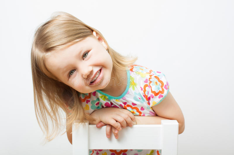 Funny smiling little girl. Funny smiling little girl sitting on a chair. Isolated over light gray background stock photos