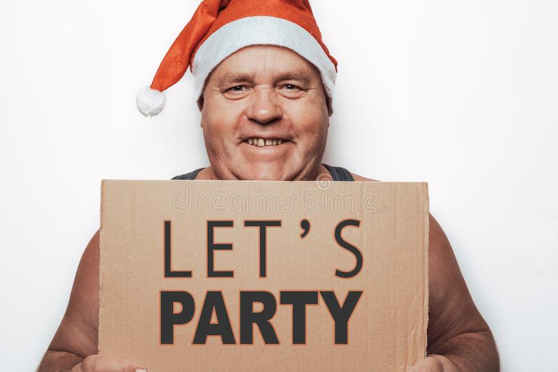Funny smiling mature man in red Santa Claus hat holding in hands cardboard with inscription - Let`s Party stock photo