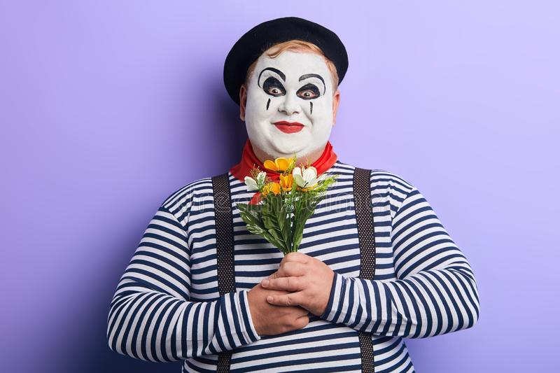 Funny smiling mime holding flowers and looking at the camera royalty free stock photos