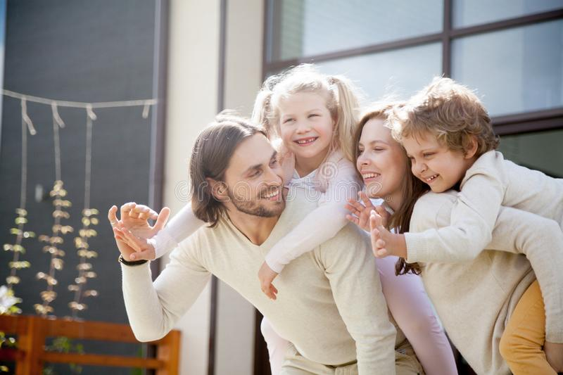 Funny smiling parents and little children outdoors stock photos