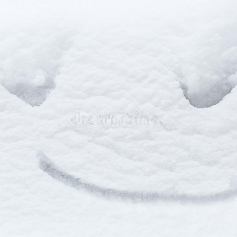 Funny snow smile painted on the white snow background, happy winter concept stock images