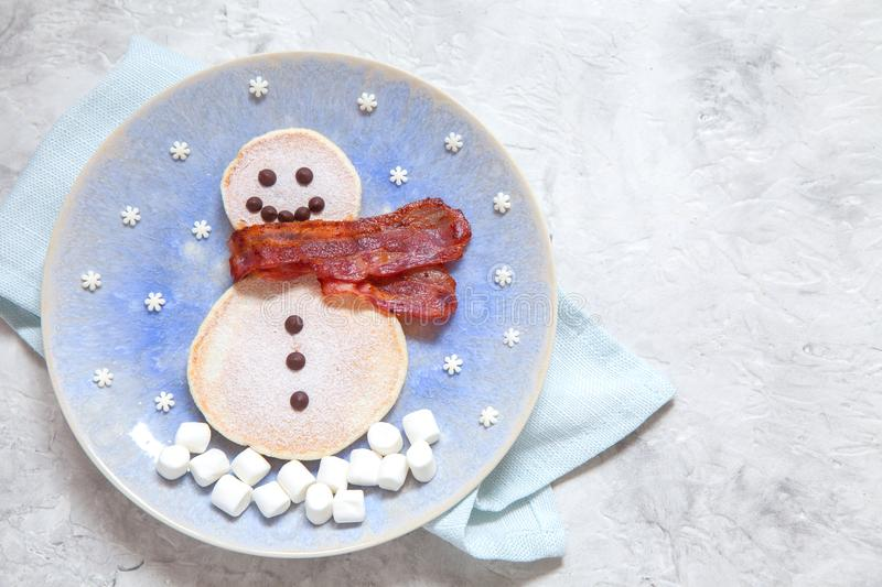 Funny snowman Christmas morning breakfast pancakes for kids. Funny snowman Christmas morning breakfast pancakes and bacon for kids royalty free stock photography
