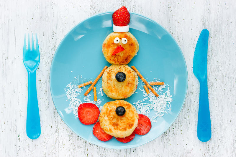 Funny snowman Christmas morning breakfast pancakes for kids. Top view stock photo
