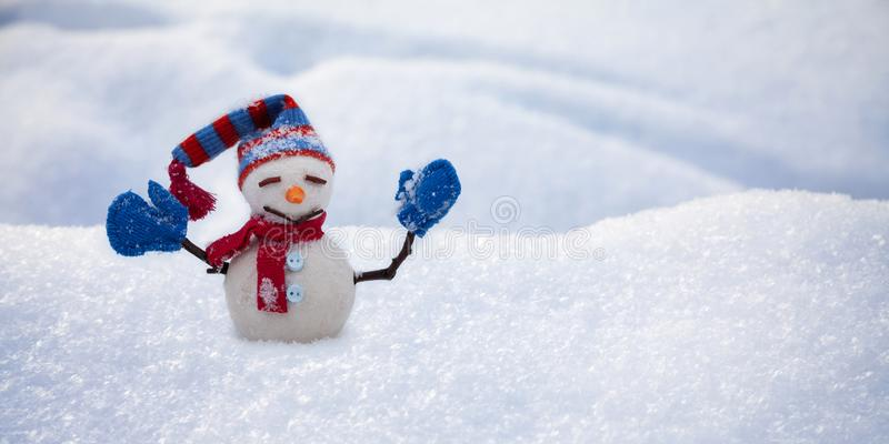 Funny snowman with hat red scarf and blue mittens, natural snowy field background. Happy New Year and Merry Christmas stock photo