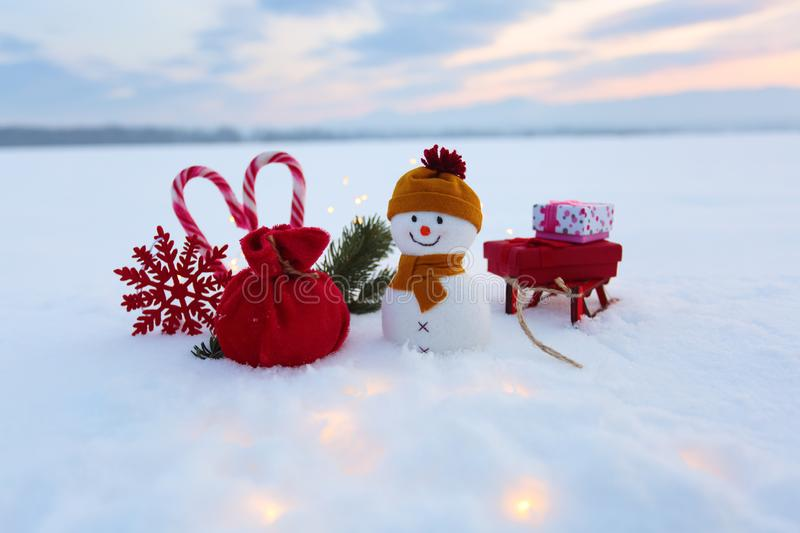 Funny snowman with sledges and colorful boxes with presents. Garlands enlighten the snow. New Year and Christmas concept with snow. Y background. Winter scenery stock photo