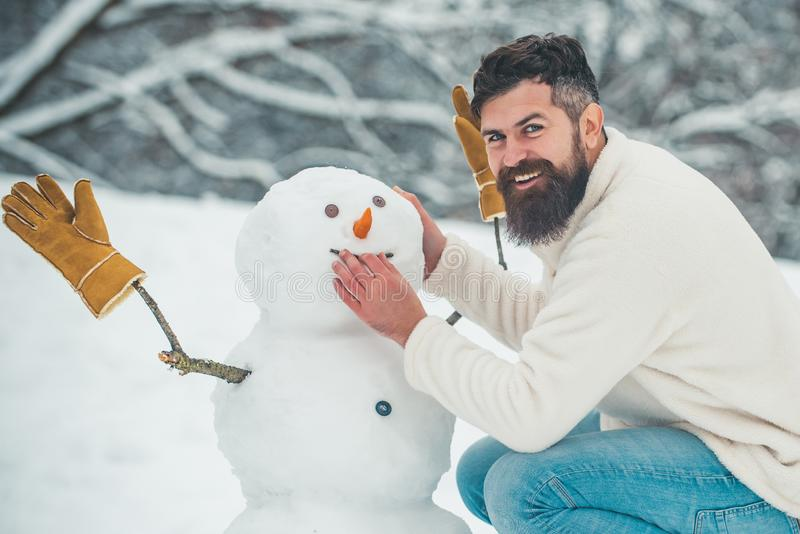 Funny snowmen. Happy smiling man make snowman on sunny winter day. People in snow. Snowman. Handsome Winter Man with stock photos