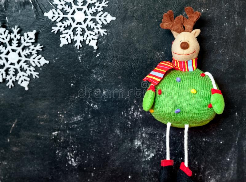 Funny soft elk toy and white snowflakes on dark background stock photo