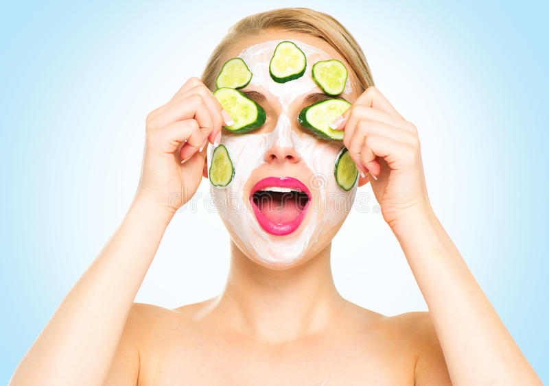 Funny spa woman applying fresh facial mask stock photography