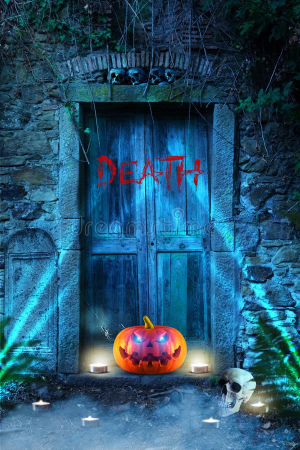 Funny spooky halloween pumpkin with spider, skulls and candles in front of a cemetery. royalty free stock photos
