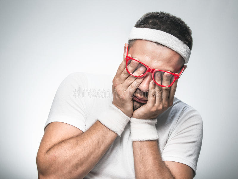 Funny sport man. Sleepy funny sport man does not wish to doing fitness - exercising. Isolated on gray background. Studio shot stock photos