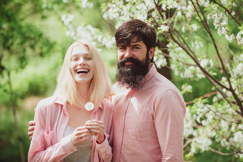 Funny spring couple blow dandelion. Lovely couple in spring garden. stock photography