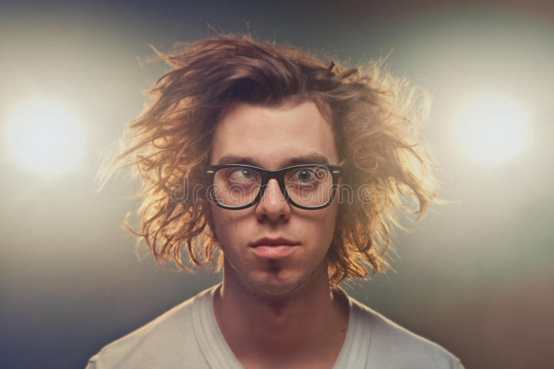 Funny Squinting man with Tousled brown hair in studio. Using spotlights in background stock images