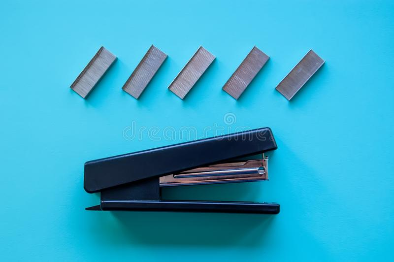 Funny stapler and paper clips on blue background.  royalty free stock photography