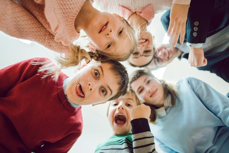 Funny students and teacher as a team in class room of school. Sticking tongues out stock images