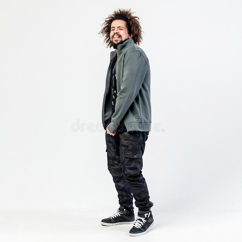 Funny stylish curly guy with a beard dressed in a black t-shirt, gray jacket, khaki pants and sneakers poses in the stock photo