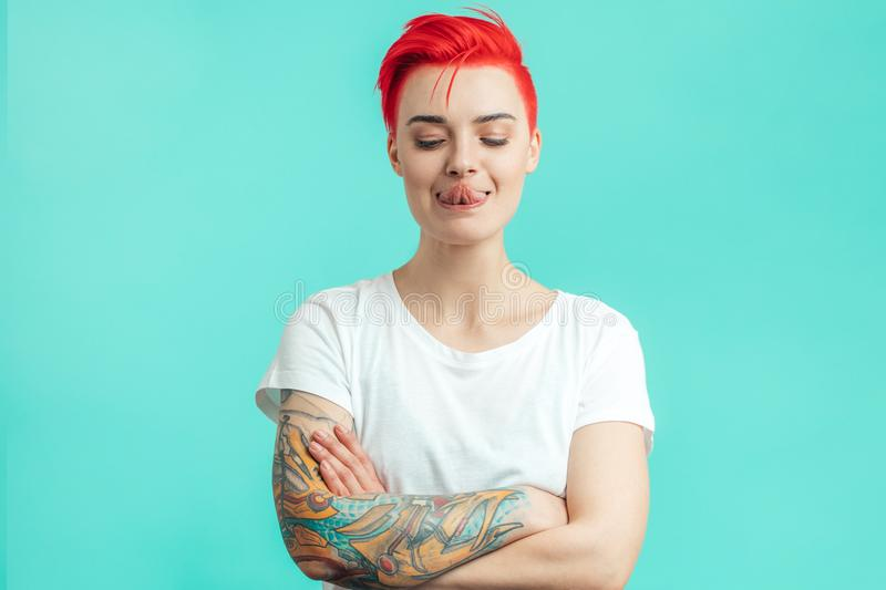 Funny stylish girl trying to touch her nose with tongue royalty free stock photos