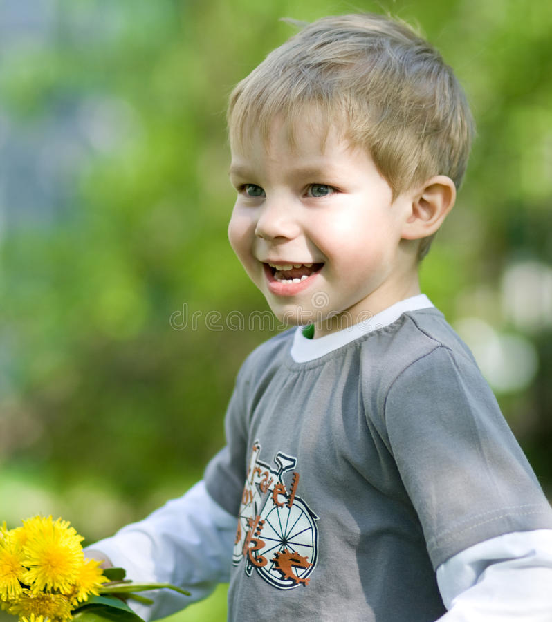 Funny summer. Happy kid with dandelions in summer park stock images