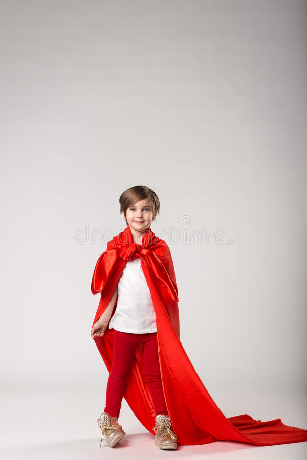 Funny superhero girl in red cape. Superman kid concept royalty free stock photo