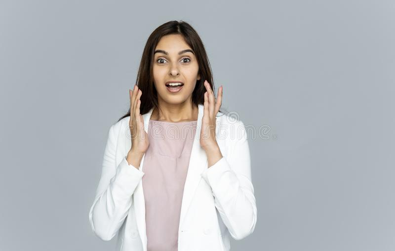 Funny surprised indian business woman look at camera isolate on grey background stock photography