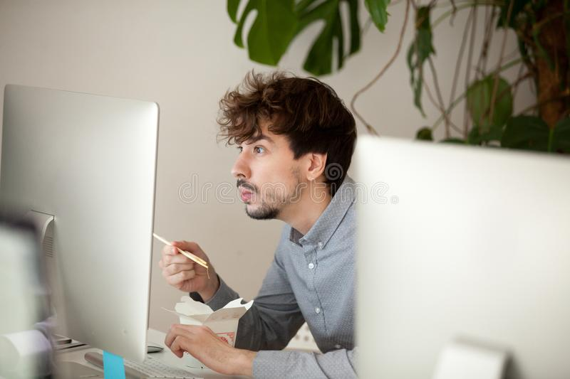 Funny surprised employee eating chinese food looking at computer stock photos