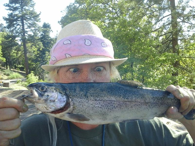 Funny Surprised Woman Catches Large Fish Oncorhynchus mykiss royalty free stock images