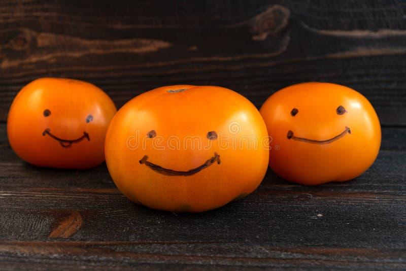 Funny team bonding team building success concept. Three fresh orange tomatoes on dark wooden desk board stock images