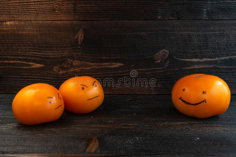 Funny team bonding team building success concept. Three fresh orange tomatoes on dark wooden desk board royalty free stock images
