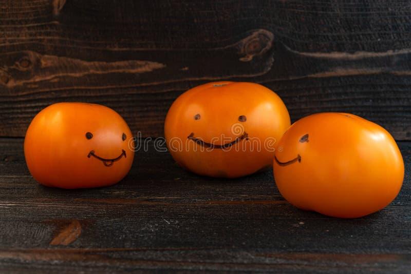Funny team bonding team building success concept. Three fresh orange tomatoes on dark wooden desk board royalty free stock image