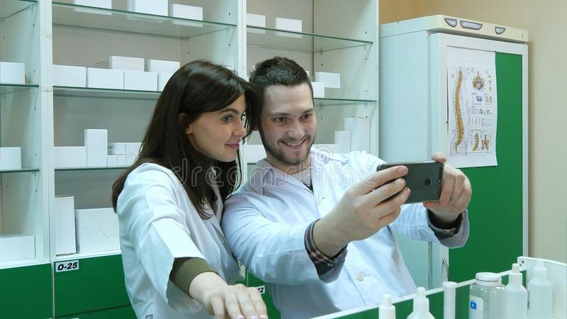 Funny team of pharmacist making selfie pictures at pharmacy. Close up. Professional shot in 4K resolution. 081. You can use it e.g. in your commercial video royalty free stock image