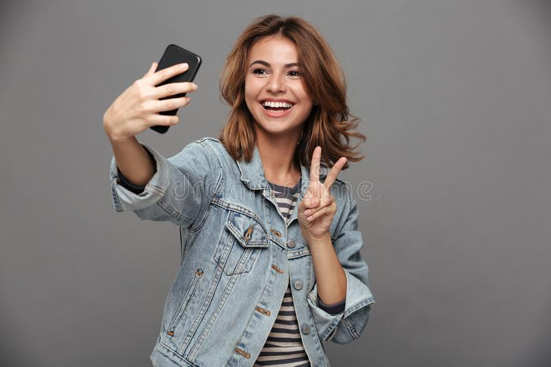 Funny teen girl in jeans jacket showing peace gesture while taking selfie on smartphone stock images