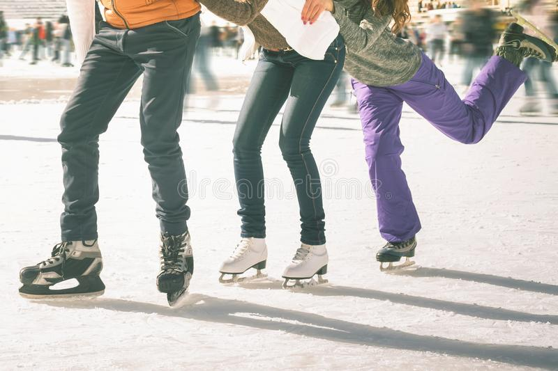 Funny teenagers girls and boy skating outdoor, ice rink. Image of ice-skaters group funny teenagers. Ice skating outdoor at ice rink, looking at camera. Ice royalty free stock photography