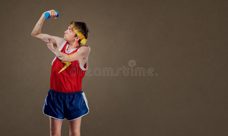 A funny, thin freak guy in sportswear with dumbbells showing musles royalty free stock images