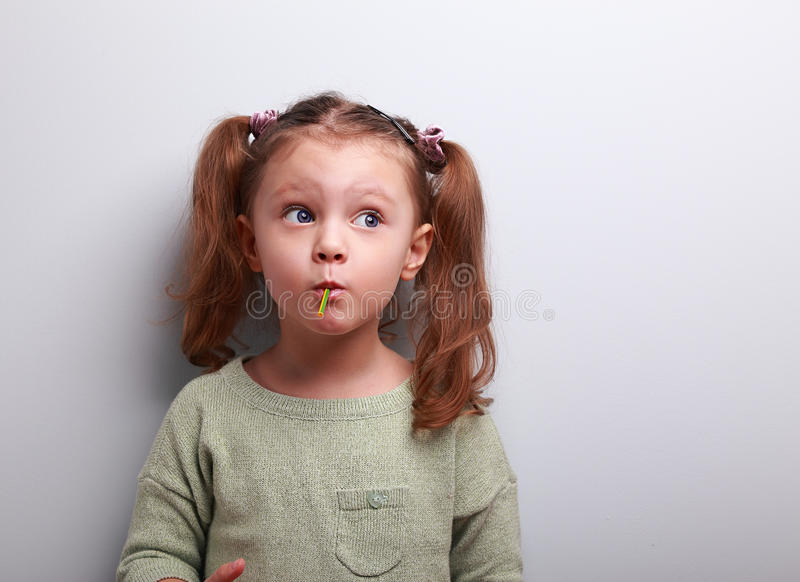 Funny thinking kid girl eating lollipop and looking up royalty free stock images