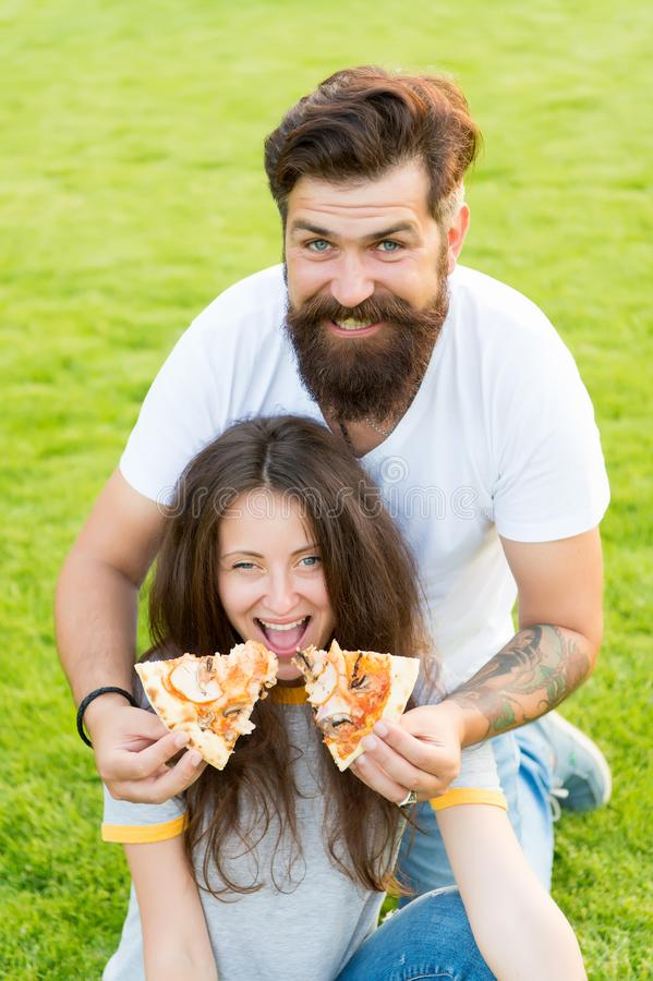 Funny time. summer picnic on green grass. Diet. happy couple eating pizza. Healthy food. couple in love dating. hunger stock photo