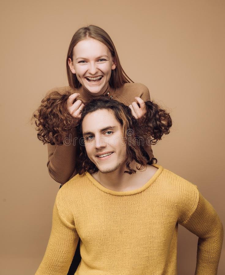 Funny time together. Joyful moments in pairs. Cheerful girl holding curly hair of boyfriend makes him funny hairstyles. royalty free stock photos