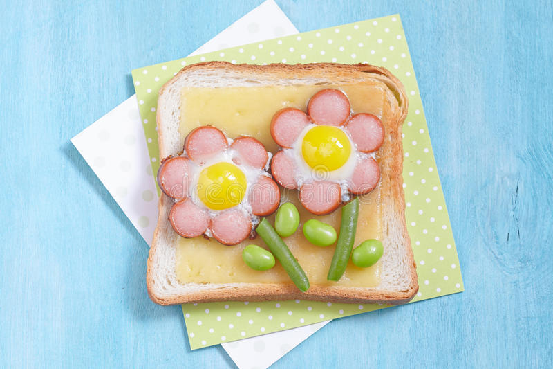 Funny toast with cheese, sausages, quail eggs and edamame. Funny toast with cheese and flower made of sausages, green beans and quail eggs royalty free stock photo