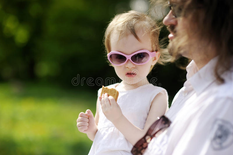 Funny toddler girl eating cookie