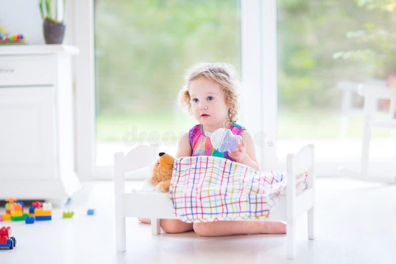 Funny toddler girl feeding her toy bear in sunny room stock photos