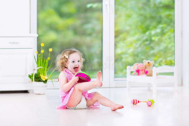 Funny toddler girl playing tambourine in white room. Cute curly laughing toddler girl in a pink dress playing tambourine and maracas in a sunny room with a big stock photo