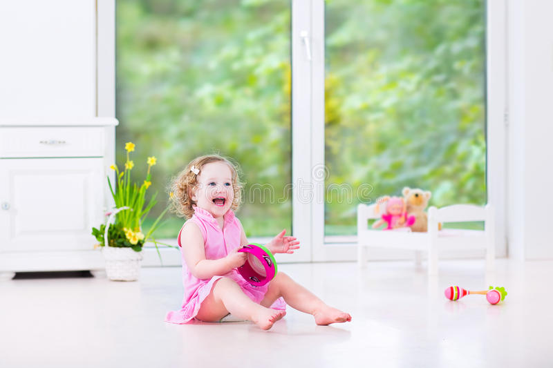 Funny toddler girl playing tambourine in white room. Cute curly laughing toddler girl in a pink dress playing tambourine and maracas in a sunny room with a big royalty free stock photos