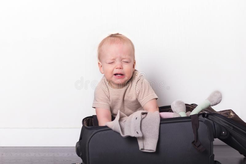 Funny toddler sitting in the suitcase and trying to pack it. Cute baby boy going to vacation royalty free stock images