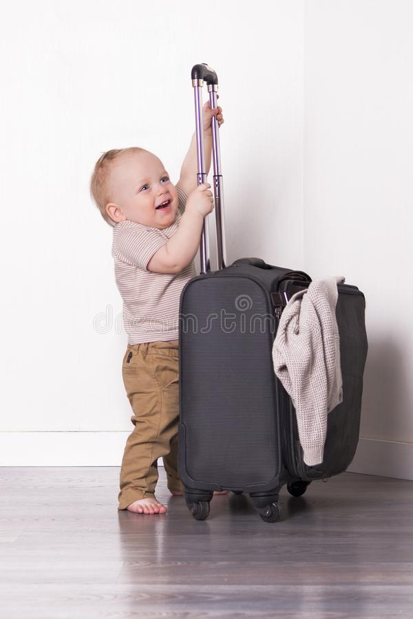 Funny toddler with suitcase. Cute baby boy going to vacation stock photography