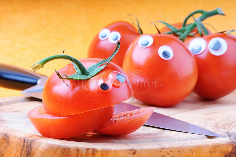 Funny tomatoes with googly eyes. On cutting board stock photo